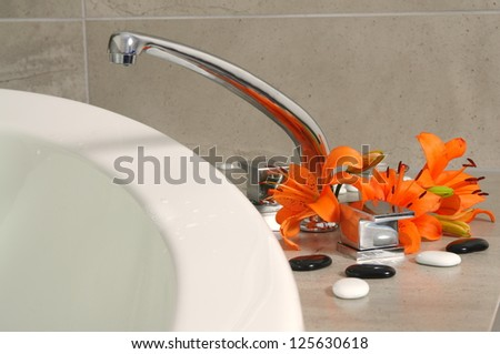 water tap with flowers in spa salon.shallow DOF - stock photo