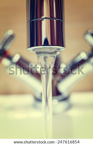 water tap with modern design in bathroom, vintage look - stock photo