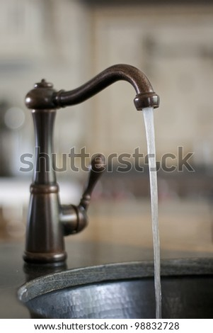 Water tap with running water, wasting water - stock photo