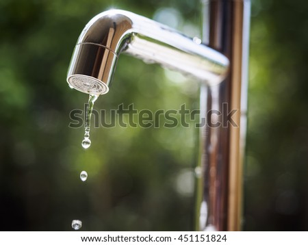 Water tap with water drop outdoor green park background - stock photo