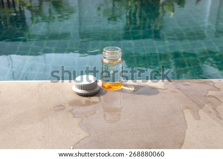 Water testing bottle with pH testing tablet center - stock photo
