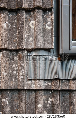 Water thermal insulation of a roof tile demonstration next ot a roof window - stock photo