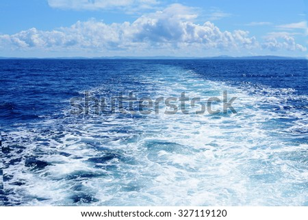 Water thrust behind a boat going to horizon - stock photo