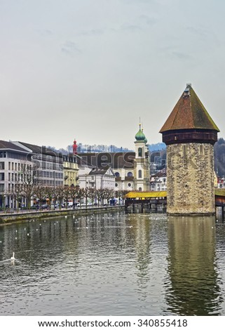 Water tower of a famous Chapel Bridge in Lucerne. Jesuit church seen in the background. Switzerland. Europe. - stock photo