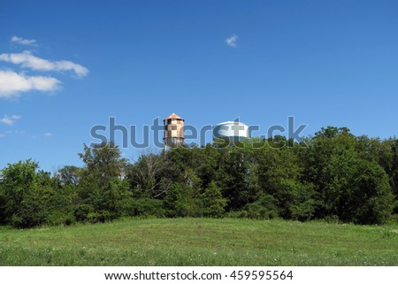 Water towers just beyond the trees on a beautiful sunny day