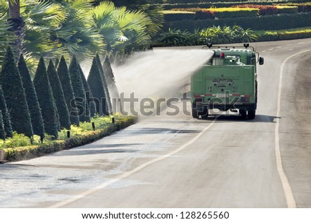 Water truck watering bush and shrub in park