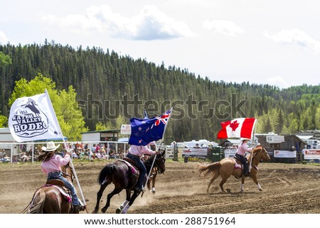 WATER VALLEY, CANADA - JUN 6 2015: Unidentified flag bearers opens the  Bucking Horse Competition in Water Valley. This annual event is important in the rural as well as the sport loving community.  - stock photo