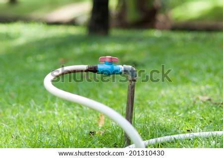 Water valve with hose in garden at morning - stock photo