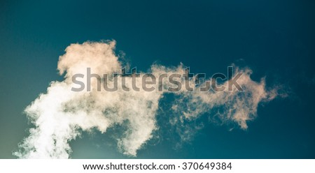 Water vapor backlit by the sun against a blue sky - stock photo
