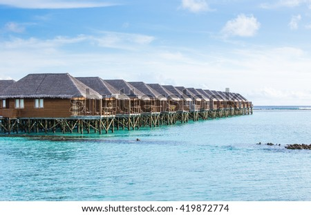 Water Villas (Bungalows) on the Perfect Tropical Island, Beautiful white sand on Tropical beach blue water and  blue sky, Maldives islands - stock photo