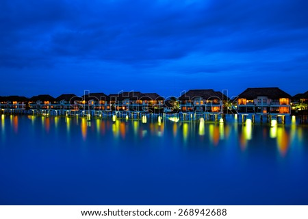 Water villas making reflections in the ocean at sunset - stock photo