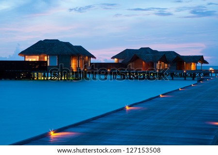Water villas on Maldives in the evening - stock photo