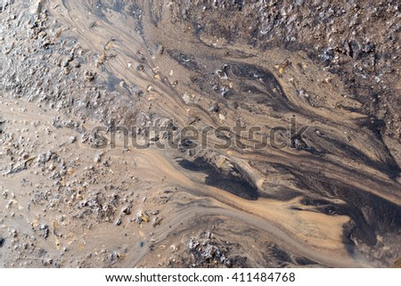 Water washes mud and grime to create natural patterns on the surface of a sand and stone based background - stock photo