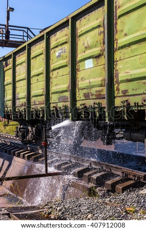 water washing of old freight railway cars - stock photo
