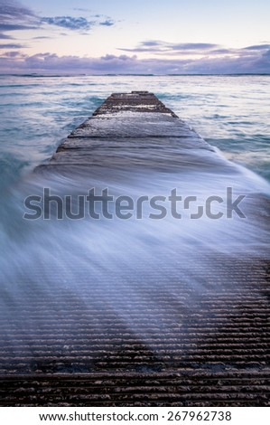 Water washing over a breakwater on famous Waikiki beach in Honolulu Hawaii. - stock photo