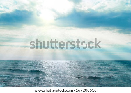 Water, waves and clouds. Sunset above the sea with sunbeams. - stock photo