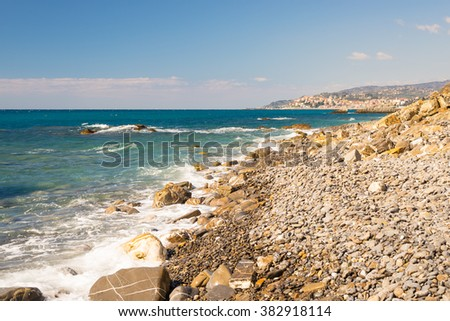 Water waves breaking on gravels, pebbles and boulders of an empty beach in the harsh rocky coastline of Liguria, North Italy. Clear blue sky, wide angle view. - stock photo