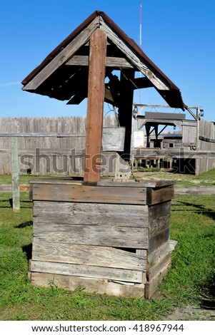 water well in front of an old wooden fence - stock photo