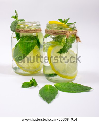 Water with fresh lemon, green leaves mint and cucumber