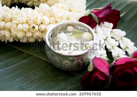 water with jasmine flower in silver bowl and jasmine garland on banana leaf background - stock photo