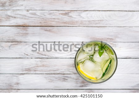 Water with lemon, mint and cucumber on the wooden light background. Water Detox. Top view. - stock photo