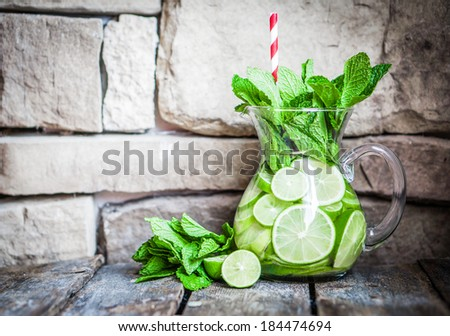 Water with limes and mint on wooden background - stock photo
