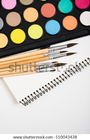 Watercolor paint set and new brushes with clean paper