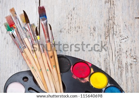 Watercolor paint with brush on wood background - stock photo