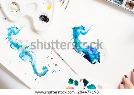 Watercolor painting of blue seahorse and artistic tools on table - stock photo