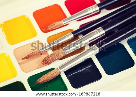 Watercolor paints and brush on the table. Vintage retro hipster style version  - stock photo