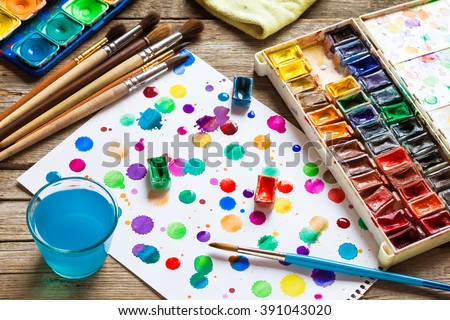 Watercolor paints, brushes for painting and paper sheet of painting on old wooden background. Top view. - stock photo