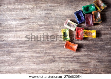 Watercolor paints on an old wooden background - stock photo