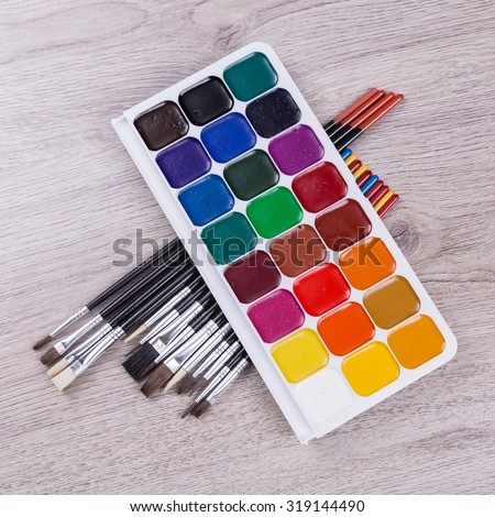 Watercolor paints with set of paint brushes on wooden background. - stock photo