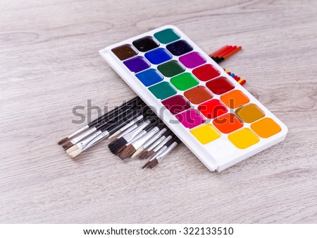 Watercolor paints with set of paint brushes on wooden background - stock photo