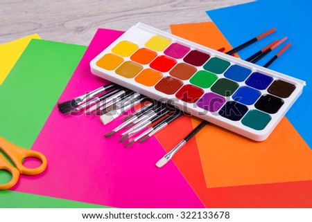 Watercolor paints with set of paint brushes on wooden background