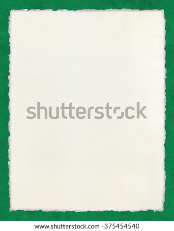 Watercolor paper with true deckled edges on a green background.  File includes a clipping path. - stock photo