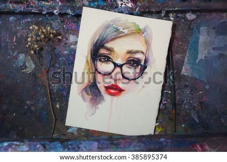 Watercolor sketch of a young girl in glasses lying on a dark artistic easel covered in paint with a brush and a plant. - stock photo