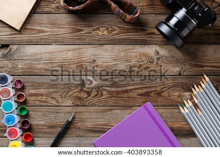 Watercolors, color pencils and sketchbook on wooden table. Flat lay photo with empty space for logo, text.  Flat lay, top view - stock photo