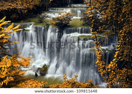 Waterfall and blue stream in the yellow forest spring season in Thailand - stock photo
