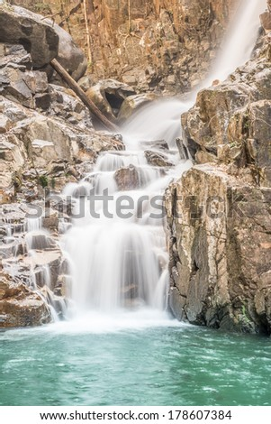Waterfall  and cliff  in the mountain on clear sky - stock photo