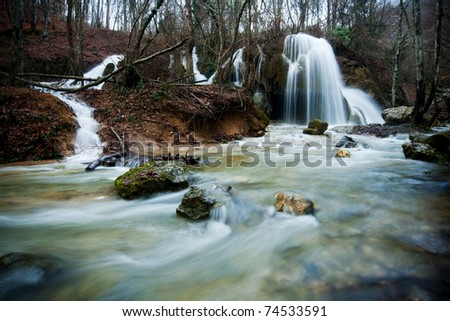 waterfall and rapid river stream among mountain autumn forest - stock photo