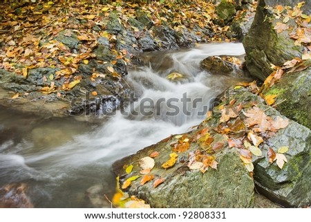 Waterfall and rocks in mountain in Autumn
