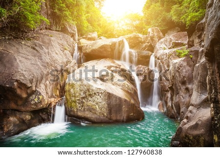 Waterfall and sun - stock photo