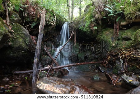waterfall between rocks covered by moss