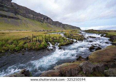 Waterfall cascades flowing into a lake in the southern region of Iceland during summer - stock photo