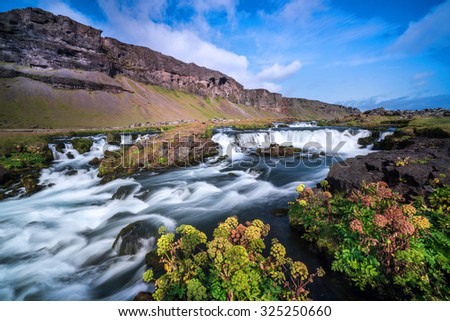Waterfall cascades flowing surrounded by colourful plants in the southern region of Iceland during summer - stock photo