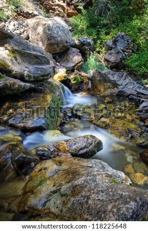 Waterfall flowing through rocks, moss and ferns in the mountains of Utah/ Summertime Waterfall - stock photo