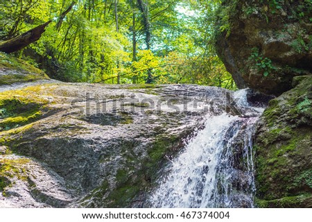 Waterfall from a cliff in the mountains. Cascade on the river. Stones covered with moss in the lake with clear water. Water in Motion. Republic of Adygea, Southern Russia.