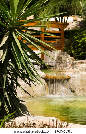 Waterfall in a beautiful tropical garden - stock photo
