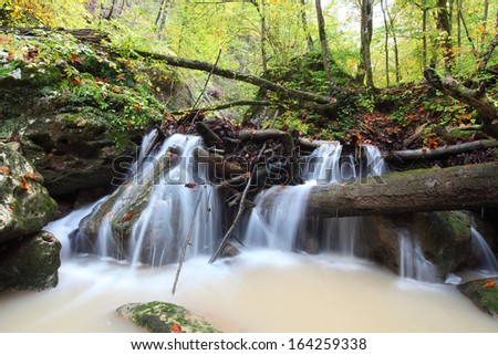 Waterfall in a forest river in autumn